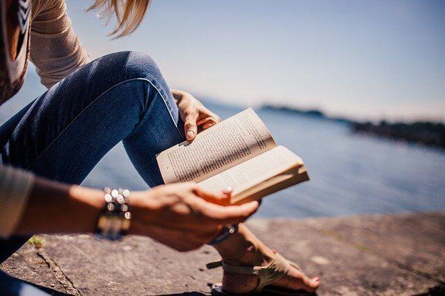 mulher com livro de autoajuda